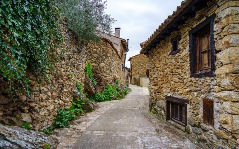 Calle estrecha llena de arquitectura tradicional en Horcajuelo de la Sierra