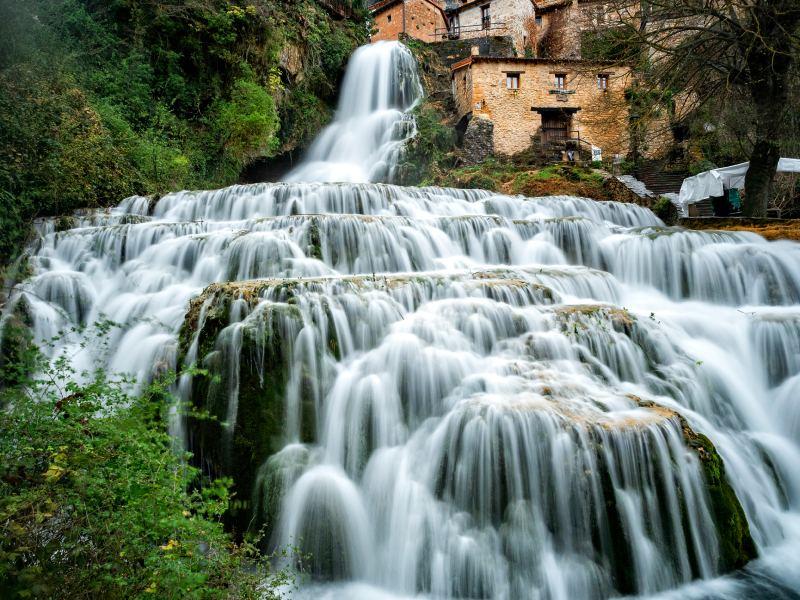 Cascada de Orbaneja del Castillo fluyendo entre el pueblo