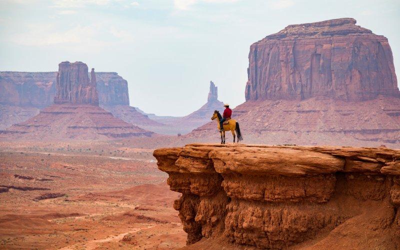 Una vaquero a lomos de un caballo en el Parque Tribal Navajo del Valle del Monumento
