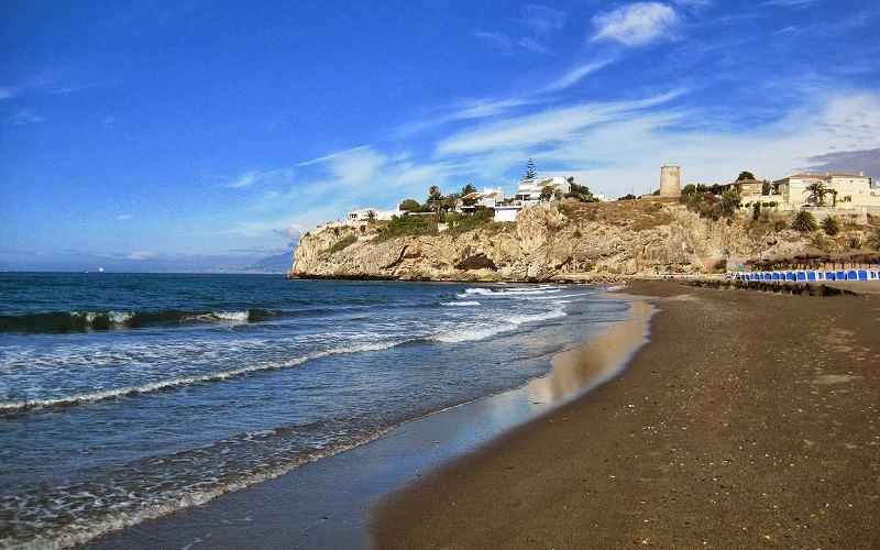 Playa con la torre del Cantal de fondo en Rincón de la Victoria
