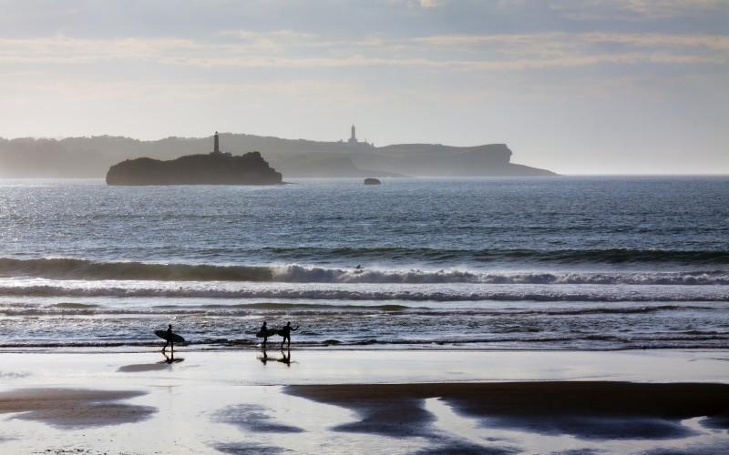 Surferos pasean a orillas de la playa de Somo